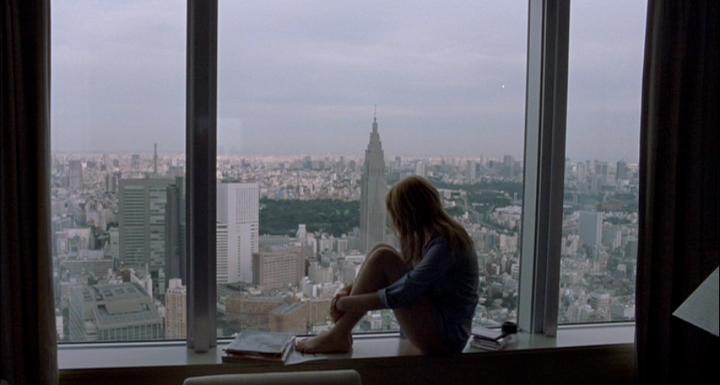 Charlotte (Scarlett Johansson) sentada no vão da janela de um quarto de hotel, observando a cidade.
