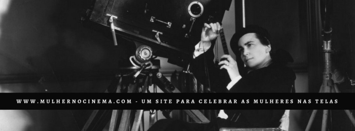 Imagem de uma mulher sentada numa cadeira de direção olhando para os negativos de um filme. Abaixo, letras brancas em um fundo preto: