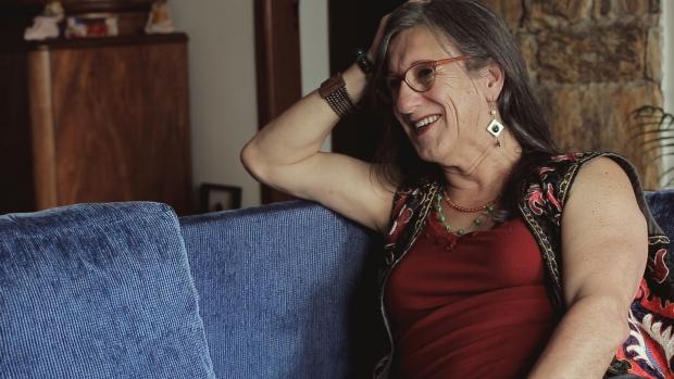 Laerte, sentada em um sofá azul, sorrindo para alguém que não está visível na cena.