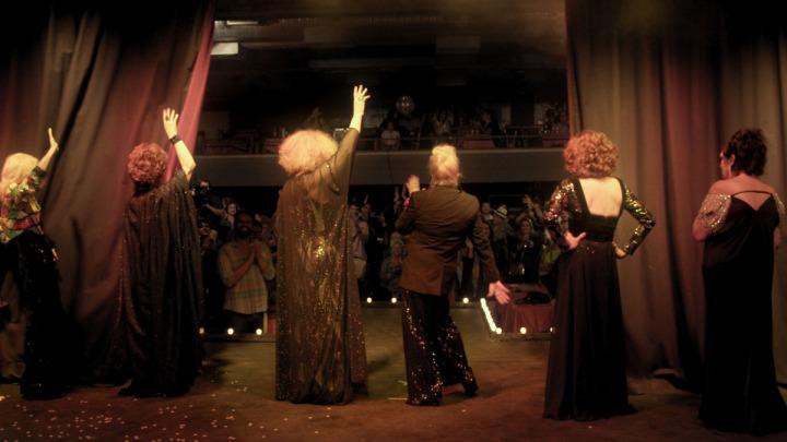 Por trás do palco, vemos as costas das estrelas do espetáculo, encarando o público.