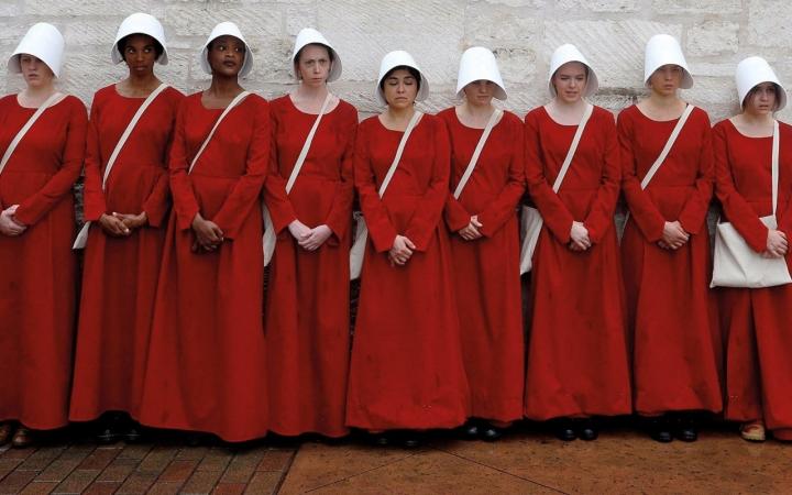 Aias, de vestido vermelho, enfileiradas em uma parede branca.