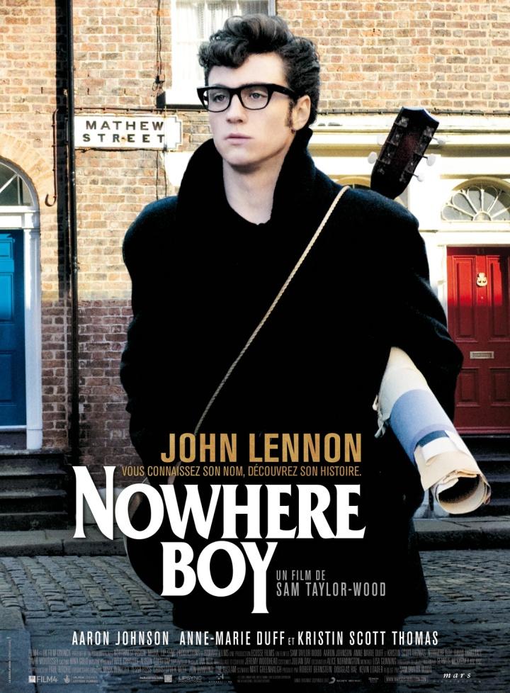 Um rapaz jovem, com casaco e óculos de aros grossos está parado na rua, com um violão pendurado nas costas e papeis embaixo do braço.