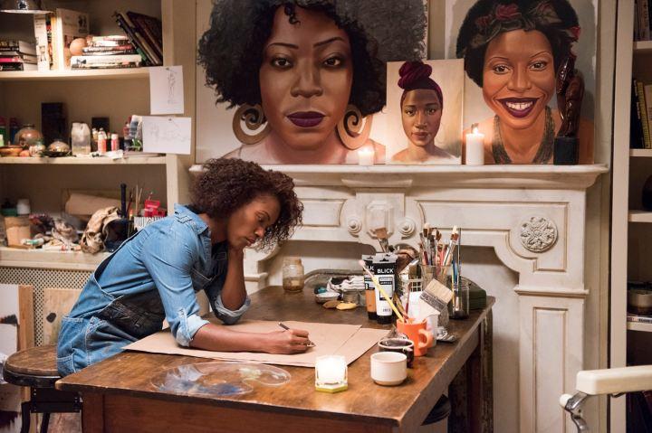 Nola desenhando numa mesa, repleta de ferramentas de pintura. Ao fundo, alguns de seus desenhos de rostos de mulheres negras