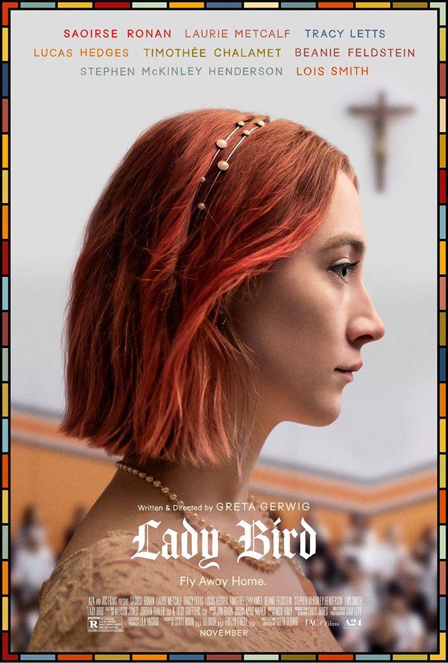 Uma menina com o cabelo pintado de vermelho está de lado, virada para a direita. Ela tem uma tiara no cabelo, um colar de pérolas e um vestido de renda. Na parede do fundo há um crucifixo.