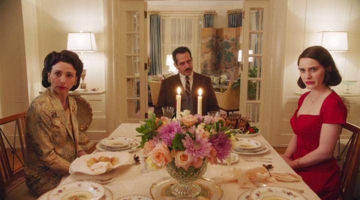 5 - Uma sala de jantar chique, com a mesa arrumada, com flores, com velas acesas e três pessoas sentadas nas cadeiras. Mãe e filha olham para algo espantadas e o homem olha zangado. To
