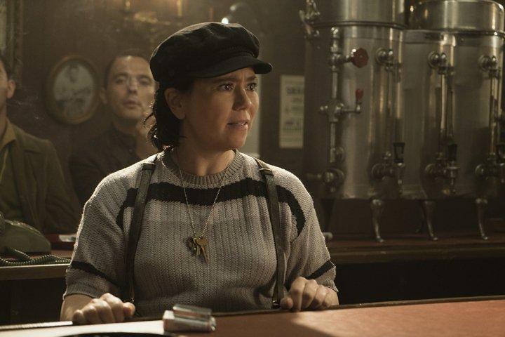 6 - Susie está atrás do balcão, usa casaco, suspensório e um quepe na cabeça. Tem chaves penduradas no pescoço e olha para algo com espanto ou incredulidade.