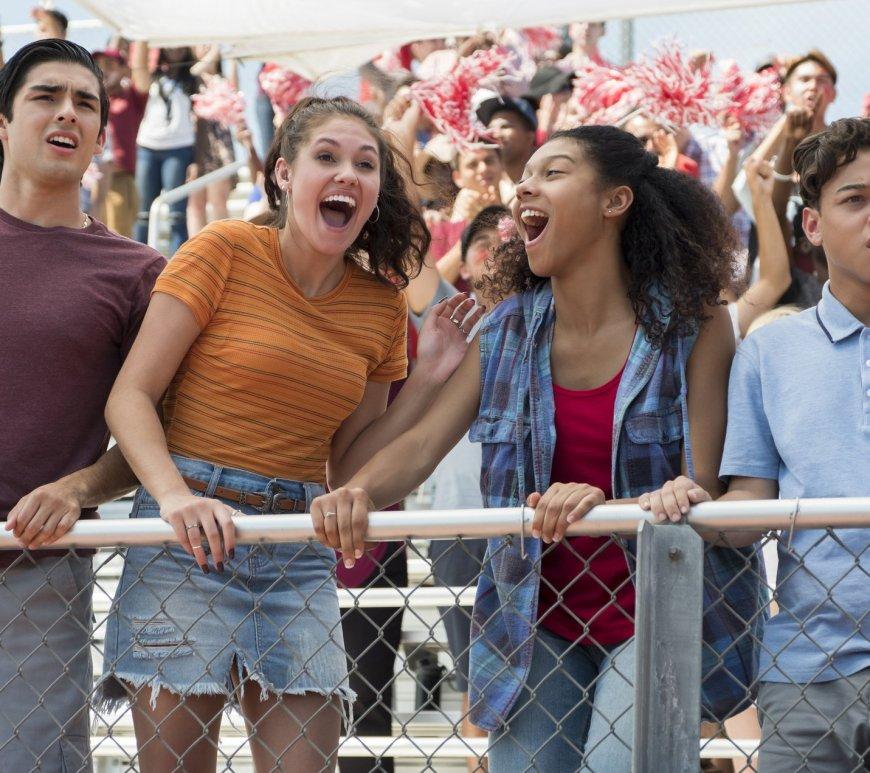 Cesar, Olivia, Monse e Ruby estão na arquibancada de um campo de esportes acompanhando um jogo. Os rapazes parecem surpresos, as garotas comemoram. A torcida atrás também acompanha o jogo.