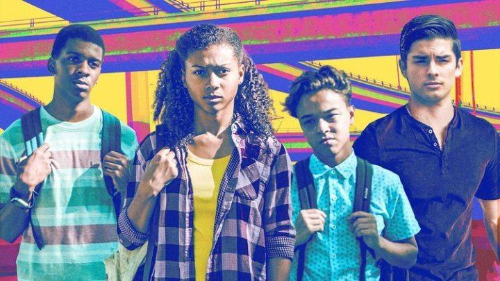 Jamal, Monse, Ruby e Cesar estão de frente para a tela, sérios, com suas mochilhas nas costas. O fundo é todo colorido.