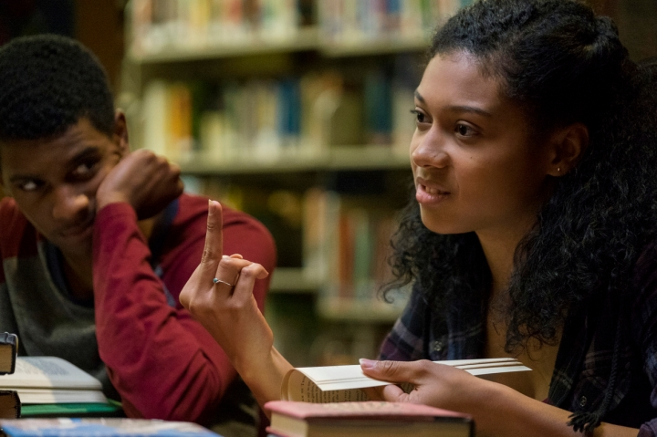 Monse e Jamal estão na biblioteca. Ela está brava com alguém que não aparece na imagem e dá dedo para essa pessoa.