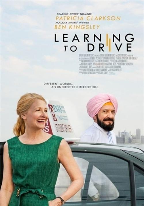 Uma mulher branca e loira sorri na frente de um taxi. Atrás do taxi está um homem indiano de turbante e gravata.
