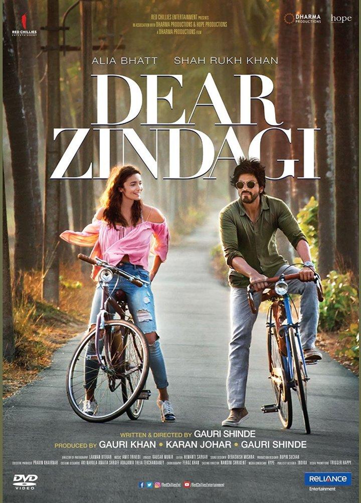 Cartaz do filme. Em uma estrada estreita, em meio a muitas árvores, um homem e uma mulher estão parados com suas bicicletas. Acima deles está o título do filme em inglês Dear Zindagi