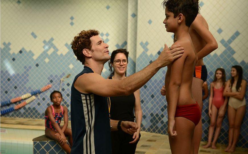 Está acontecendo uma competição de natação e várias pessoas, dentre adultos e crianças, estão reunidas em volta de uma piscina com roupas de banho. Um menino de cerca de 10 anos usa sunga e está em pé em um pódio. Ele recebe um tapinha no ombro do professor Rubens.