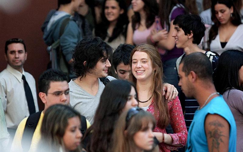 Dentre várias pessoas que andam pela rua e conversam, o foco mostra um rapaz e uma moça sorrindo. Ele está com o braço no ombro dela.