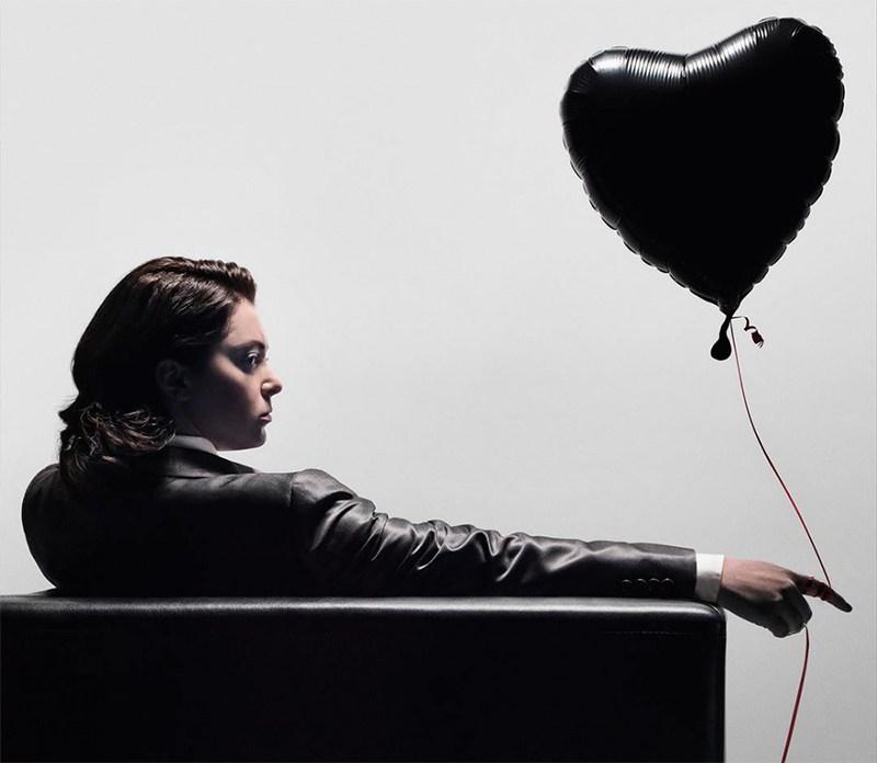Rebecca está sentada em uma poltrona meio de costas, meio de lado. Ela usa uma jaqueta e segura um balão de gás hélio em formato de coração que flutua ao seu lado. Ela está séria e tem uma expressão sombria.