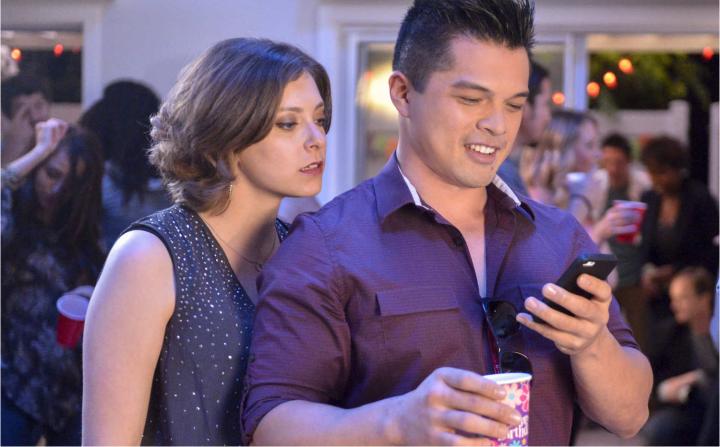 Josh está olhando seu celular e por cima de seu ombro Rebecca tenta ler o que está escrito.