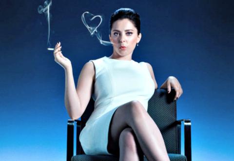 Rebecca está sentada em uma cadeira com as pernas cruzadas e usa um vestido elegante e o cabelo preso em um coque. Ela segura um cigarro e solta fumaça pela boca. A fumaça forma o formato de um coração.