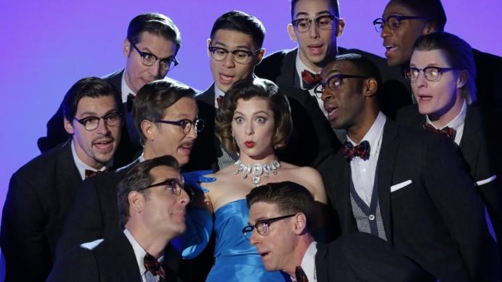 Em uma das cenas de musical, Rebecca usa um vestido chique, luvas compridas e jóias. Dez homens estão ao seu redor com ternos e óculos.