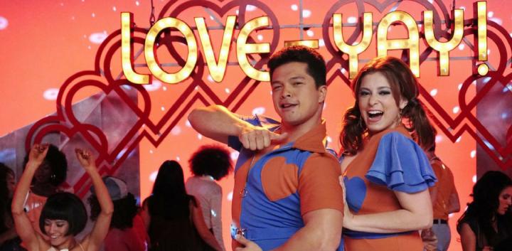 Em uma das cenas de musical, Rebecca e Josh estão com roupas chamativas no palco de um programa de auditório e sorriem para a câmera.