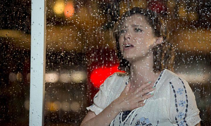 Rebecca está atrás de uma janela molhada pela chuva e olha para o lado de fora com a mão sobre o peito como se sofresse.