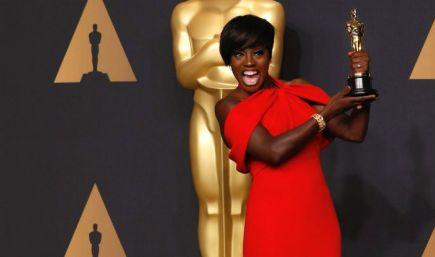 Viola Davis mostra sua estatueta do Oscar e sorri.